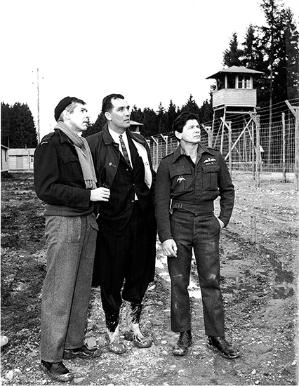 From left, James Coburn, Wally Floody, and Charles Bronson chat on the movie set of The Great Escape, built near Munich, in 1962. Photo courtesy Cathernie Heron, sister of the late Wally Floody.